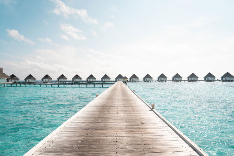 Over ocean tropical beach summer resort hotel, maldives island with sea and sky for holiday vacation