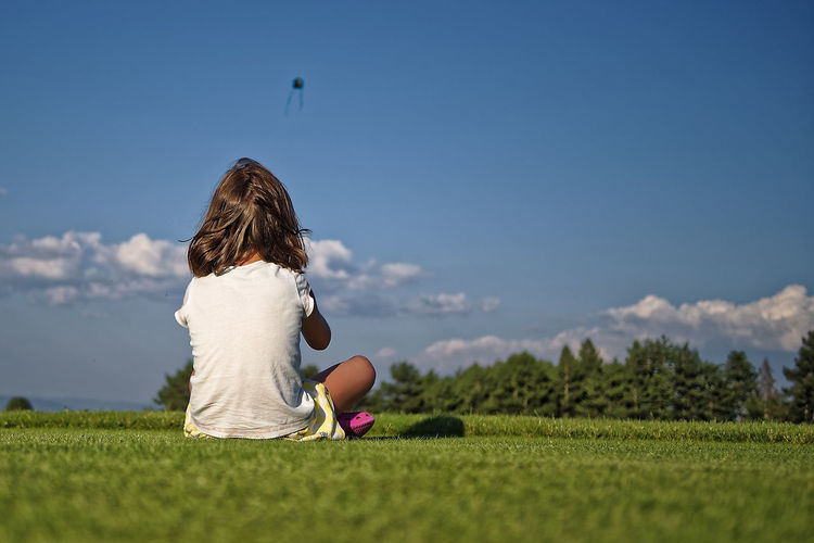 Rear view of girl sitting on field against blue sky