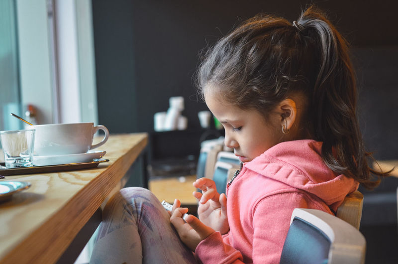 Close-up of girl using mobile phone at home