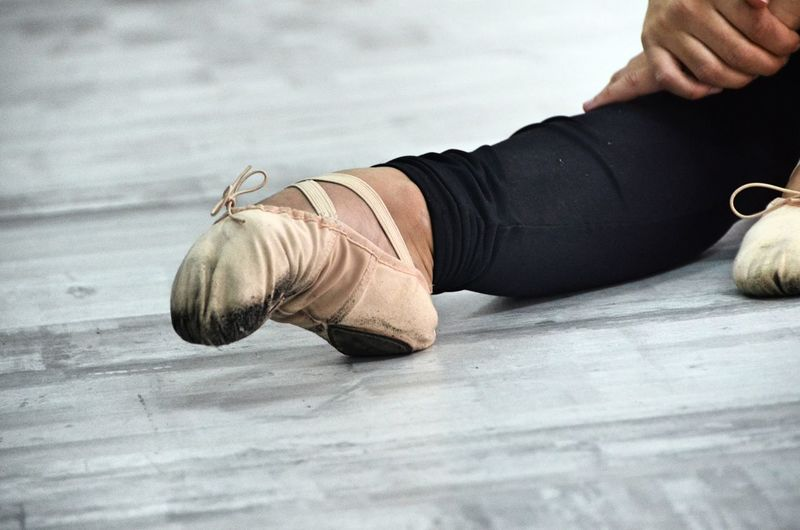 Low Section Of Ballet Dancer On Floor At Dance Studio
