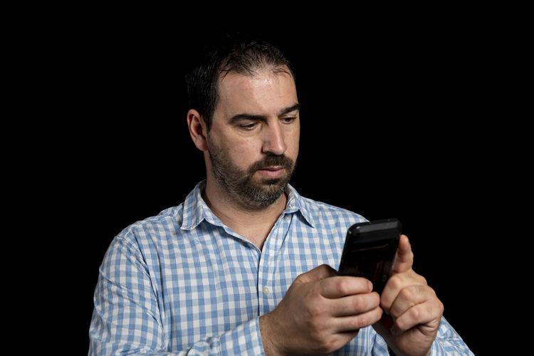Portrait of man using smart phone against black background