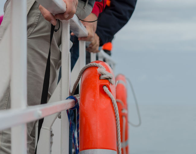 Midsection of men standing by railing with life belts on boat at sea