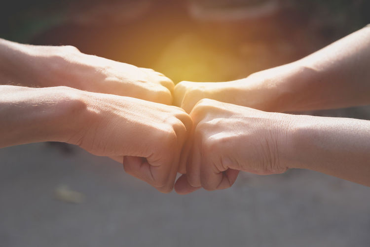 Close-up of people hands bumping fists