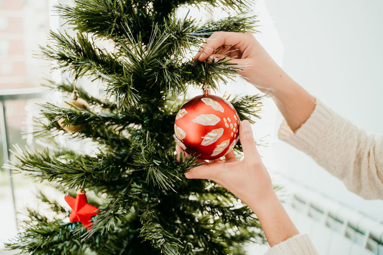 Close-up of woman decorating christmas tree at home