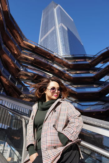 Low angle view of woman standing against building in city