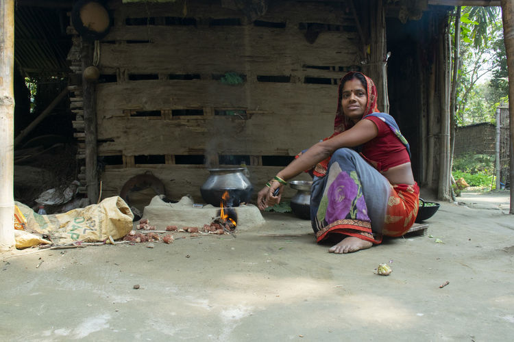Portrait of young woman sitting outdoors making food on wood burning stove