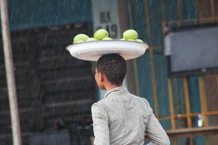 Rear view of girl carrying fruits in tray on head during rainy season