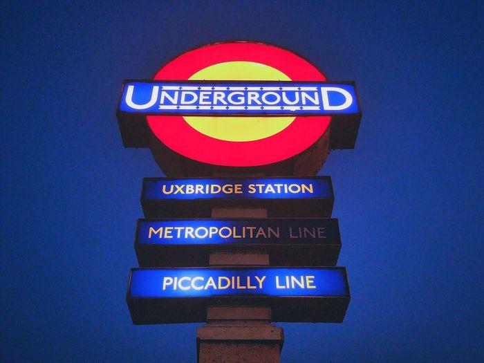 Commuting Public Transportation London Lifestyle Station Sign At The Train Station London Underground Blue Sky At Dusk