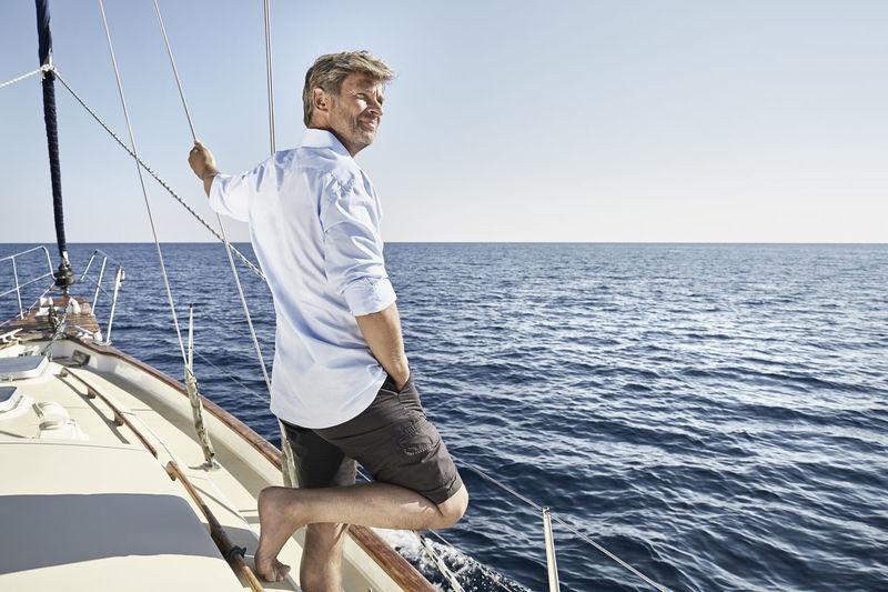Man sailing on sea against sky