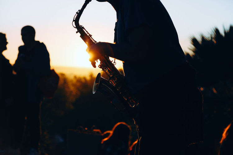 Man playing a saxophone at sunset with an orange sun hiding behind the hill in the background. Analogue Sound Saxophone Man Sunset Music Concert Jazz Sound Orange Color Playing Saxophone Debod´s Temple Viewpoint Debod West Park Madrid SPAIN Chill Chillout Analogue Music Live Music
