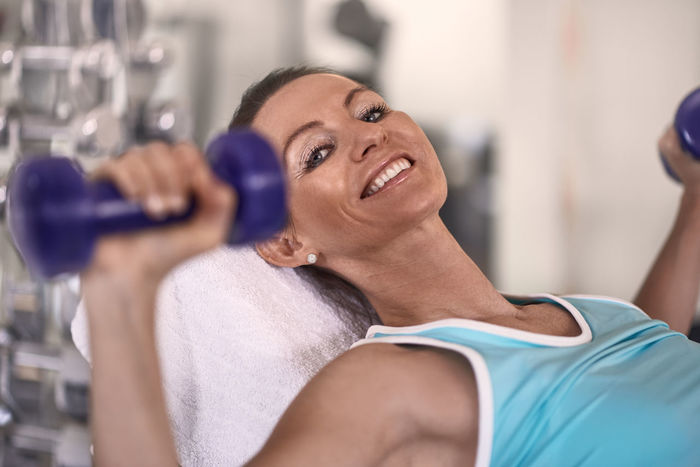 Fit middle-aged woman exercising with weights Athlete Beautiful Woman Best Ager Body Care Body Conscious Dumbbell Exercise Equipment Exercising Gym Happiness Health Club Healthy Lifestyle Indoors  Lifestyles Middle-aged One Person Real People Smiling Sport Sports Clothing Sports Training Strength Wellbeing