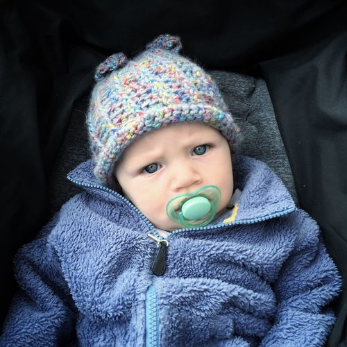Close-up portrait of cute baby girl with pacifier in mouth sitting in stroller