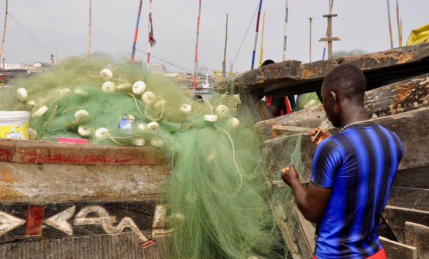 Rear view of man working over fishing net in boat