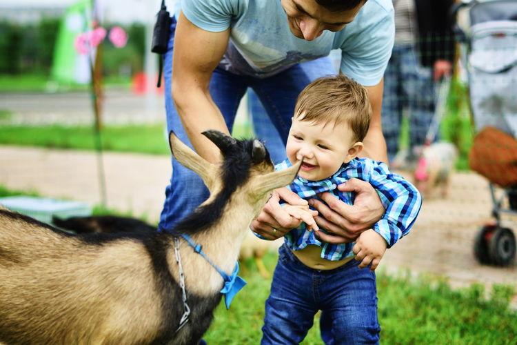Boy smiling at goat