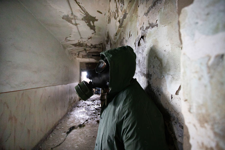 Side view of man wearing gas mask standing in abandoned building
