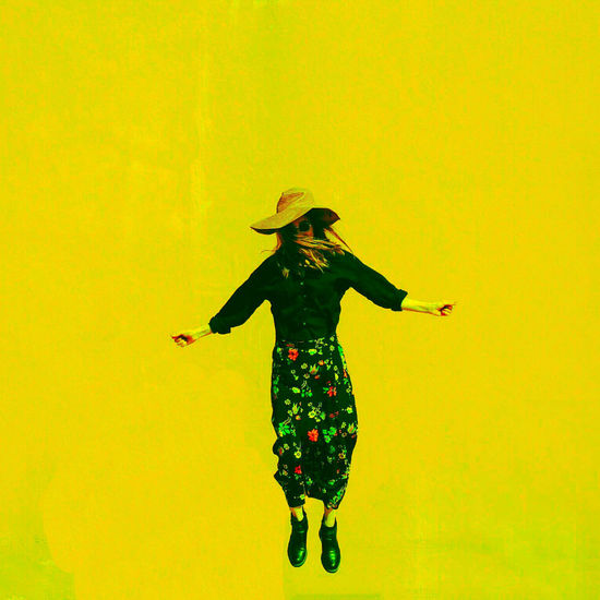 Full length of woman with arms outstretched standing against yellow background