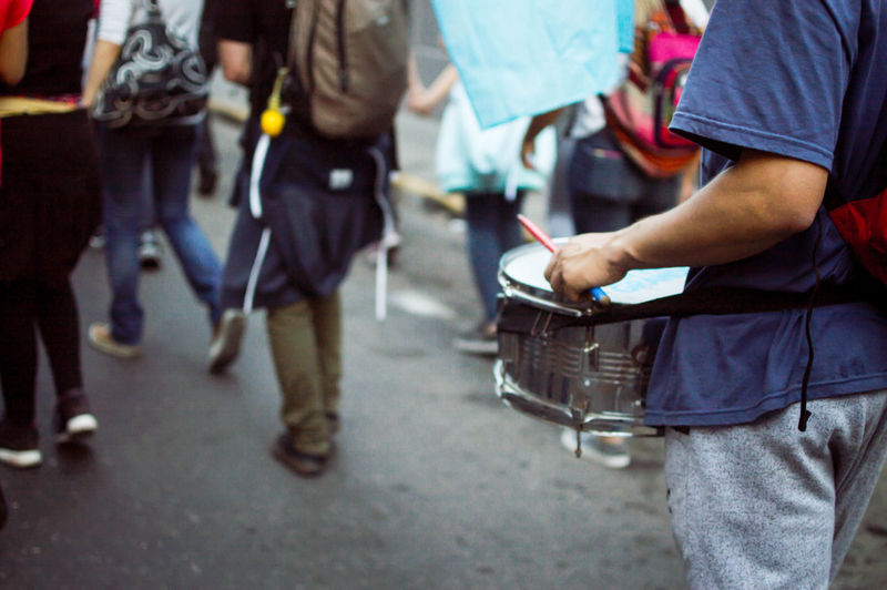 Midsection Of Man Playing Drum While Walking On Street