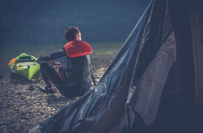 Rear View Of Man Sitting By Tent