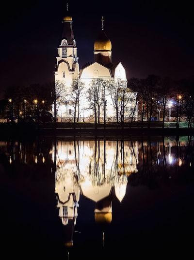 Illuminated building by lake at night