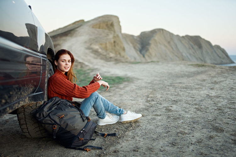 Young woman sitting on rock against mountains