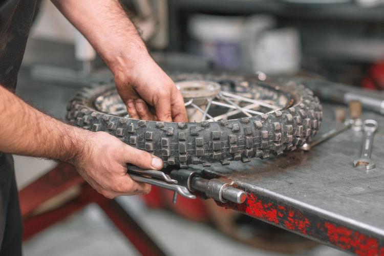 Midsection of man repairing wheel