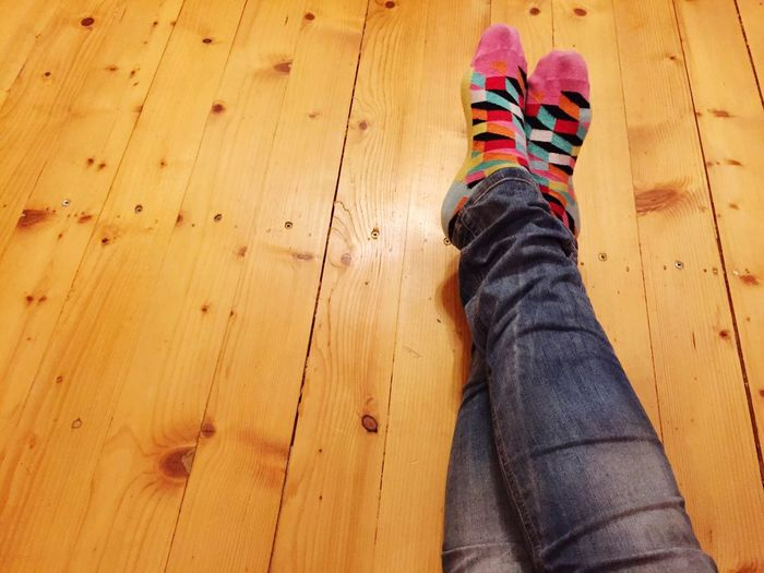 Low section of woman with multi colored socks relaxing at home