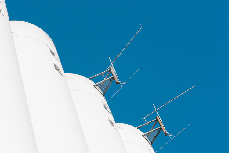 Low angle view of antennas on building against clear blue sky