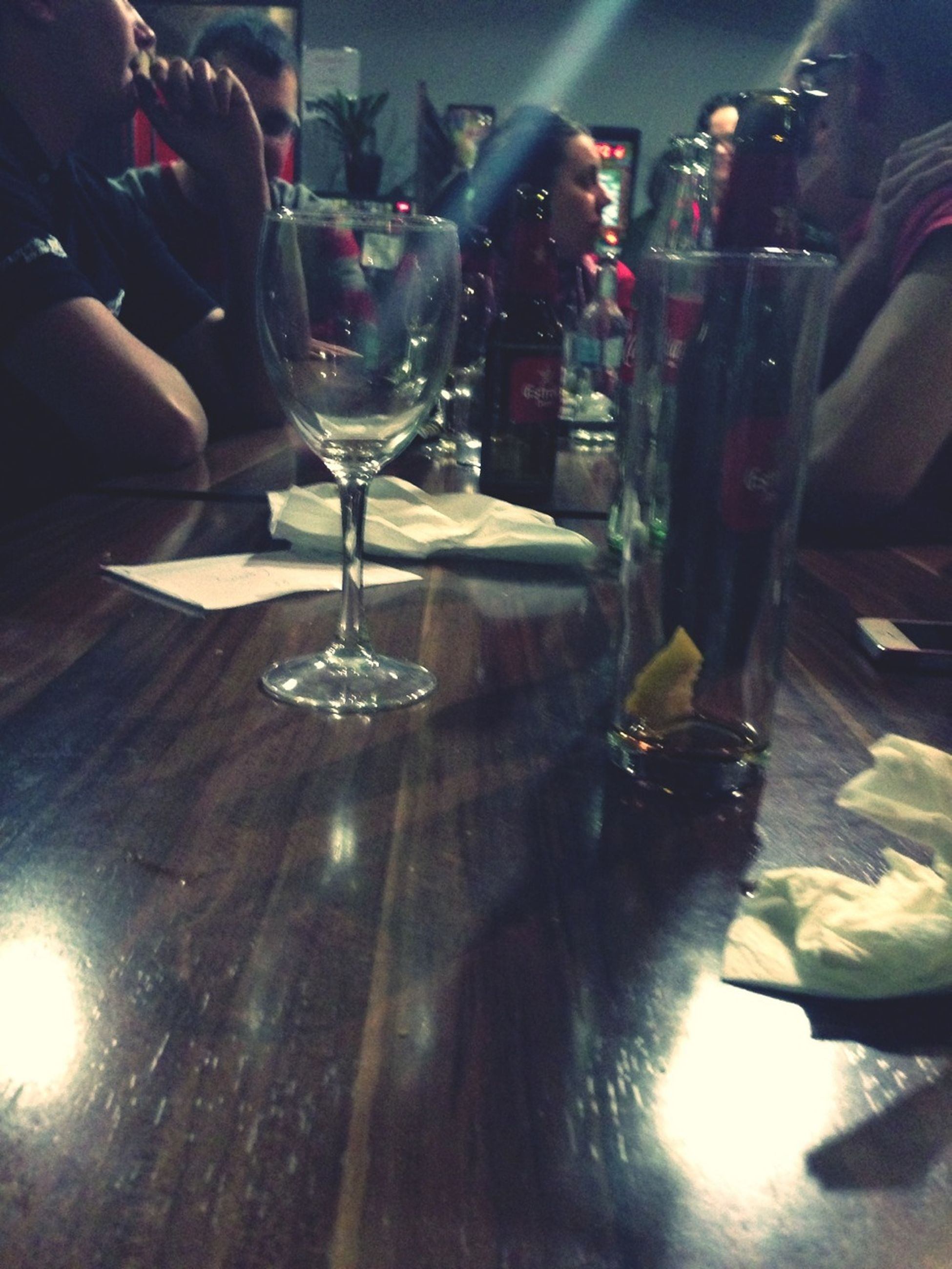 indoors, drinking glass, wineglass, glass - material, person, table, lifestyles, men, drink, leisure activity, unrecognizable person, illuminated, part of, alcohol, food and drink, incidental people, restaurant