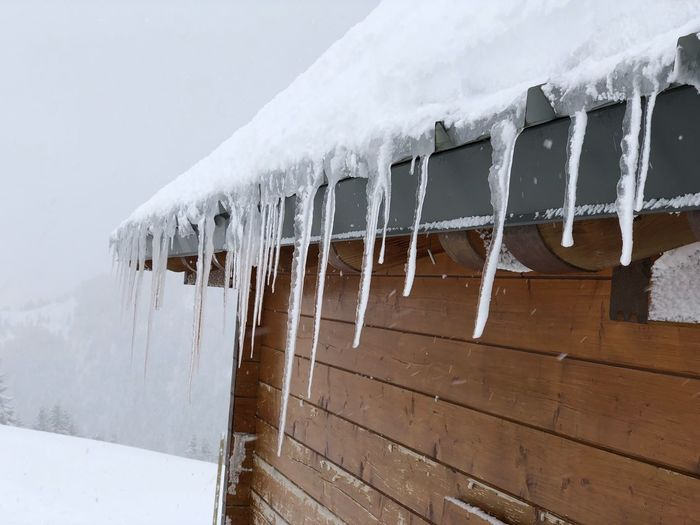 Close-up of icicles on roof against snow during winter
