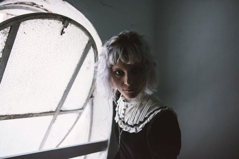Portrait of woman standing against window at home
