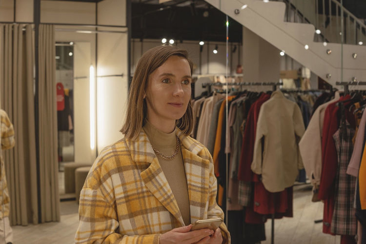 Woman trying on a coat in a fitting room of a clothing store