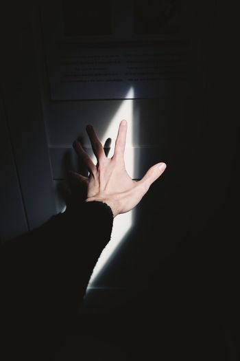 Close-Up Of Hand Reaching Towards Sunlight At Home