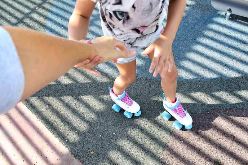 Girl learning to rollerskate Retro Rollerskating Sunshine Holding Hands Child Girl Followme Childhood Learning Park Mother Fun Outdoors Sunlight Lifestyles Looking Down