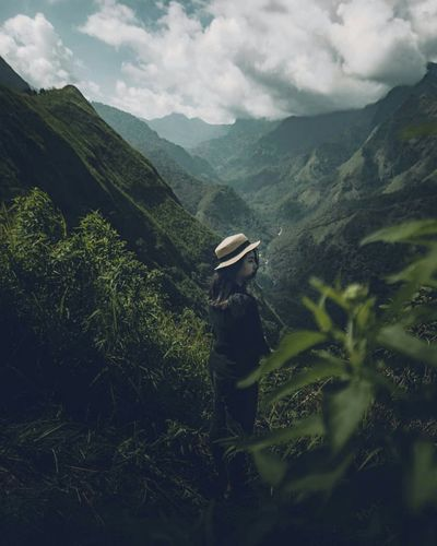 Woman standing amidst plants against mountains