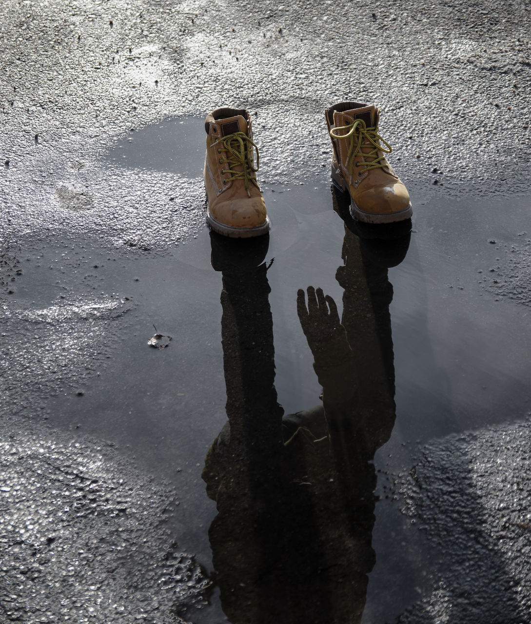 HIGH ANGLE VIEW OF SHOES ON WET LAND