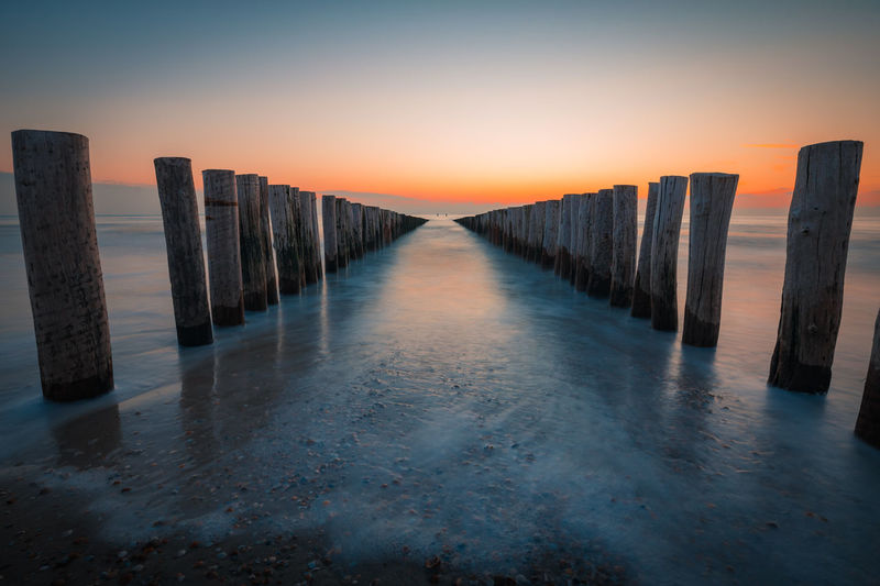 Wooden posts in sea against sky during sunset