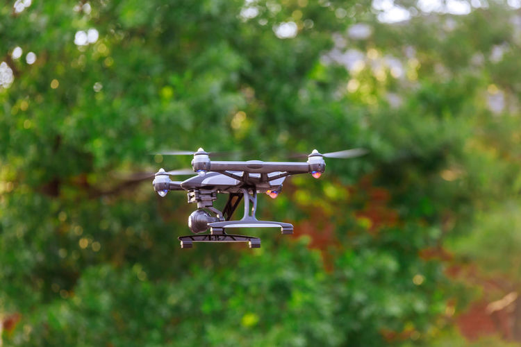 Drone Flying Against Trees