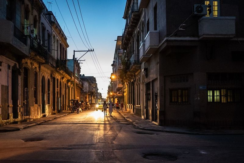 Street amidst buildings in city at dusk