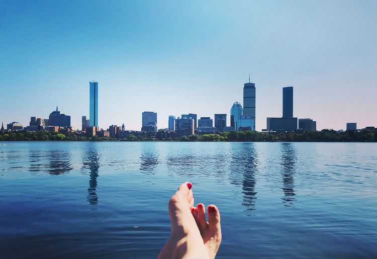 Barefoot by charles river against buildings in boston