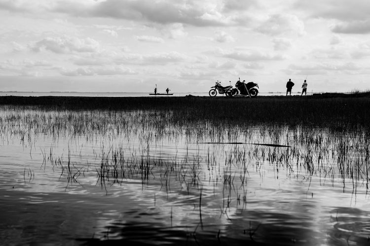 Distant view of people standing by motorcycles against lake and sky