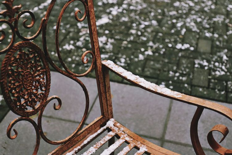 Close-up of snowy bench