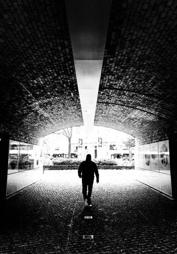 Rear view of silhouette man walking in illuminated city