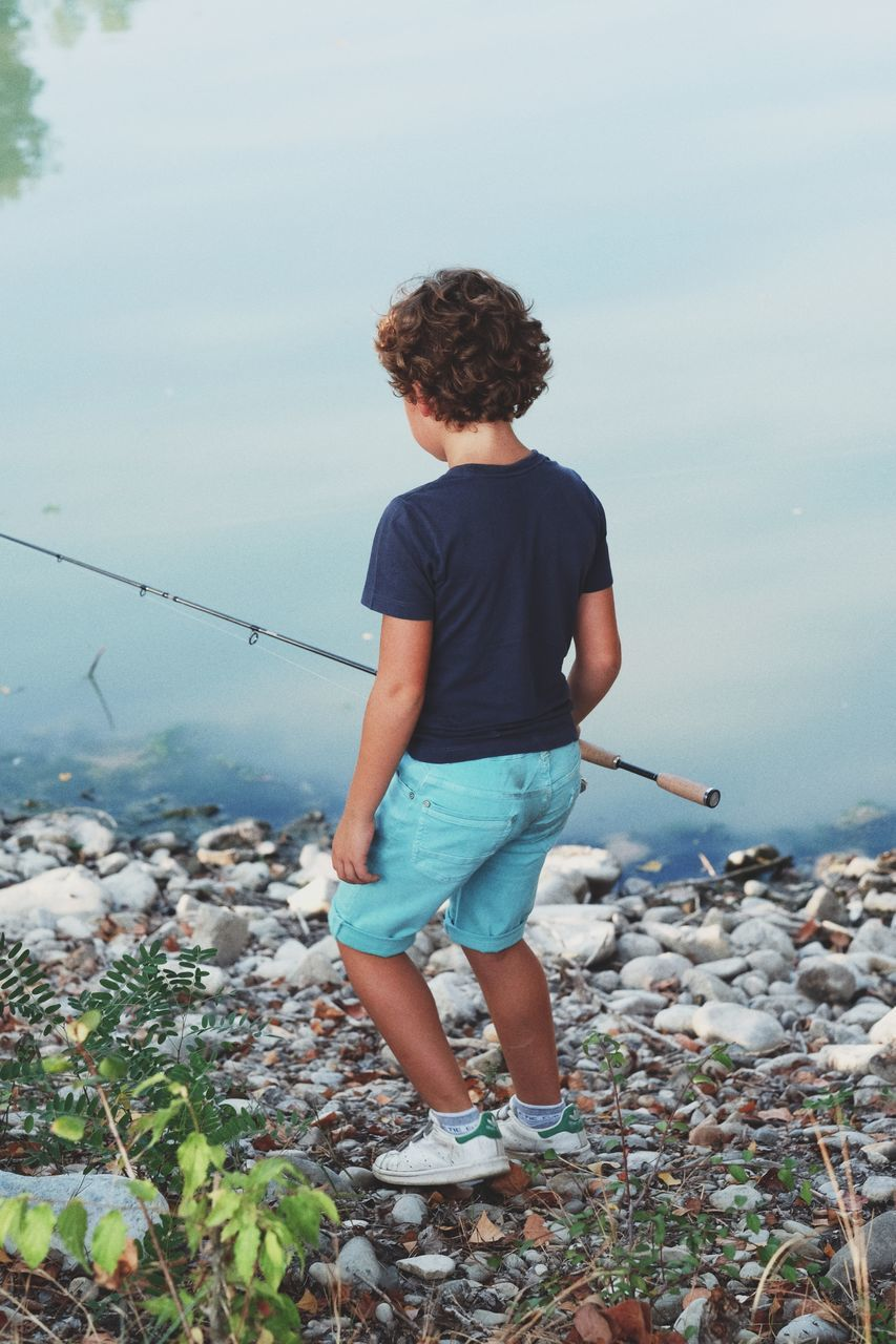 sea, water, rear view, one person, nature, real people, casual clothing, full length, outdoors, leisure activity, day, standing, beauty in nature, fishing, scenics, horizon over water, boys, sky, lifestyles, fishing pole, clear sky, people