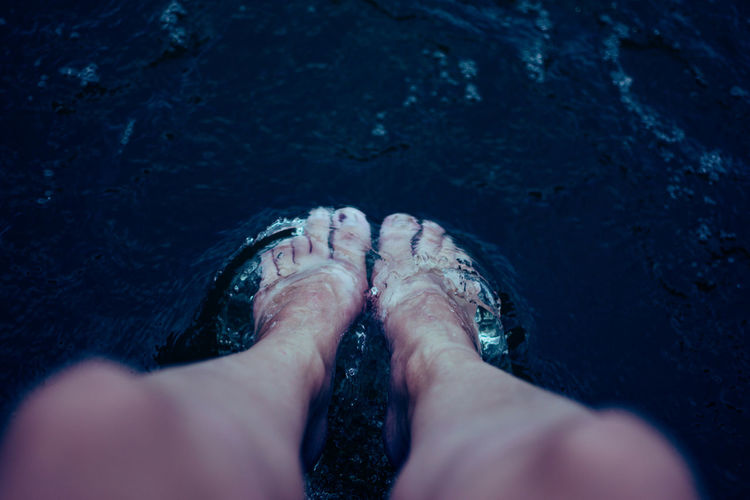 Low section of person legs in sea