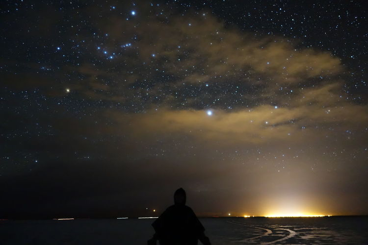 Rear view of silhouette man looking at sky at night