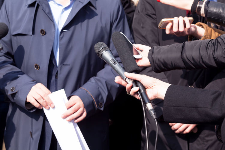 Cropped hands of journalists holding microphones in front of man