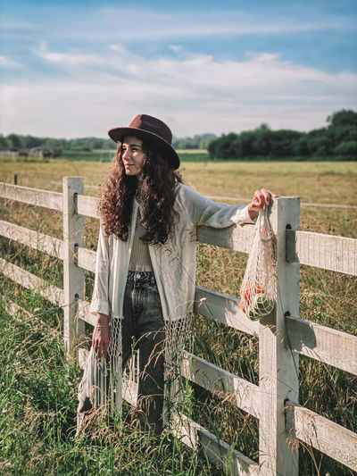 Smiling woman standing by fence on field against sky