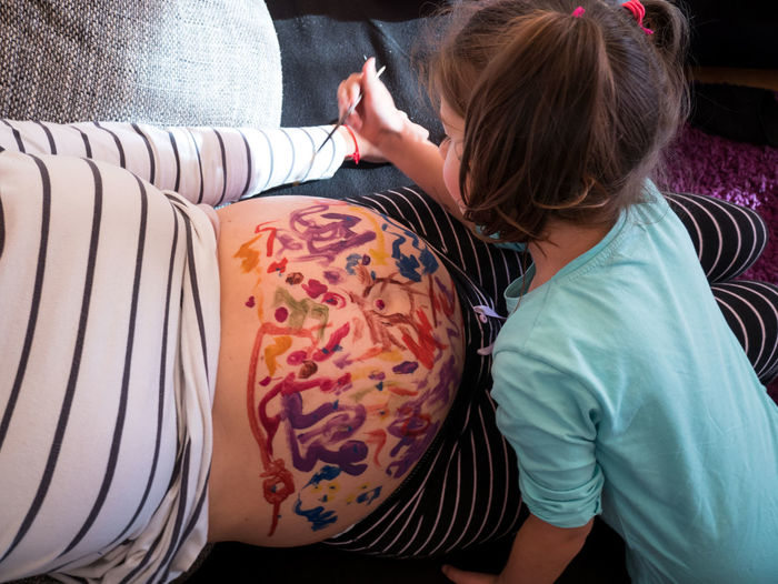 Small female kid painting mother's belly top view Family Females Fun Home Stomach Belly Casual Clothing Child Childhood Close-up Color Drawing Girls Human Body Part Human Hand Indoors  Lifestyles Painting People Pregnancy Pregnant Real People Togetherness Top View Two People