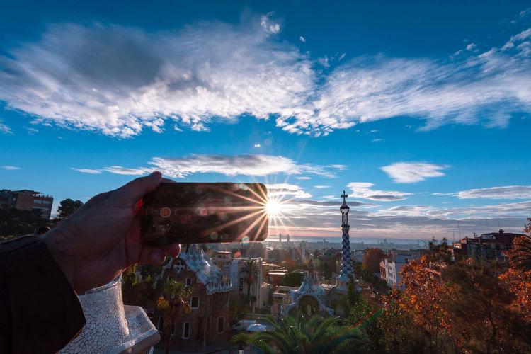 Hand holding cityscape against sky