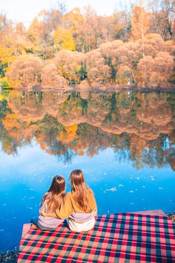 Rear view of women sitting on lake during autumn
